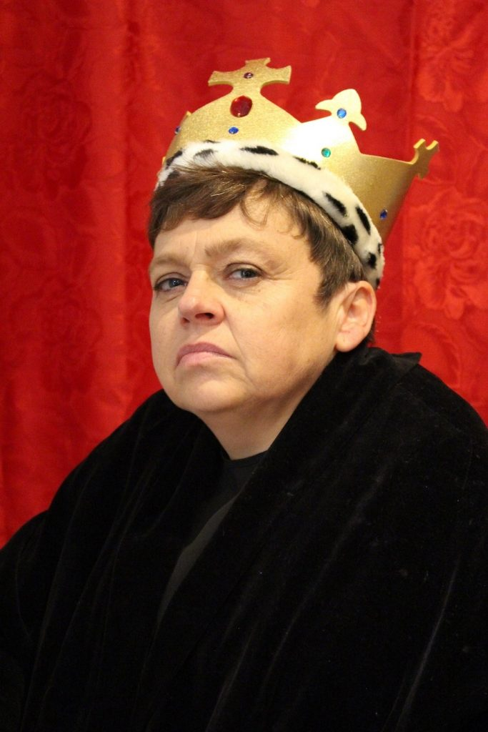 Sara Beer wears a golden crown and carries a stern pose at Richard III.
