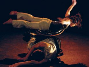 Photo of a female dance performer lying stomach-first on a male wheelchair-using dancer, lying on his side