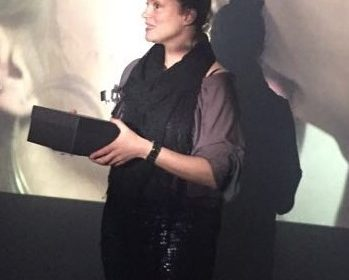 Photo of a white woman presenting in front of a screen