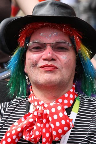 David Morris in a colourful wig and hat