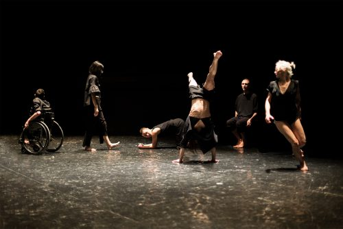 Strano ('strange' in Italian): Five dancers, some visibly disabled, some nondisabled and some invisibly disabled, dressed in black.