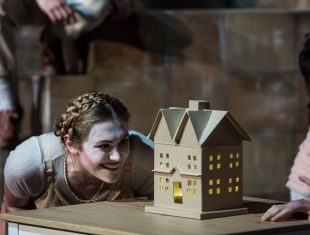Woman looks into a doll house