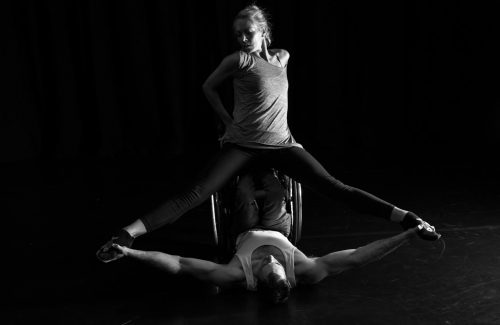 Male wheelchair dancer duet with female dancer, her legs spread as his arms are