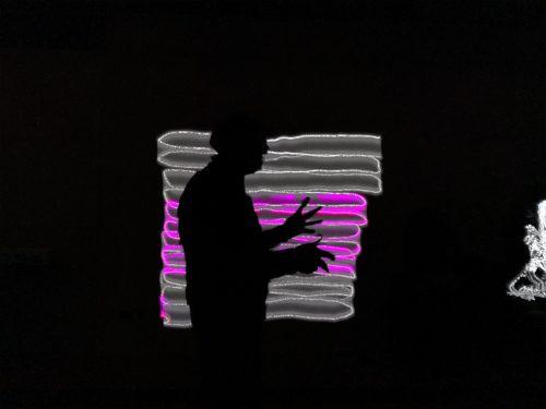 Black silhouette of the artist Damien Robinson taken against a digital light display