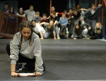 Girl kneeling reading on the floor