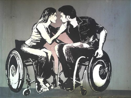 Graffiti image of a male and female wheelchair-user embracing in a kiss