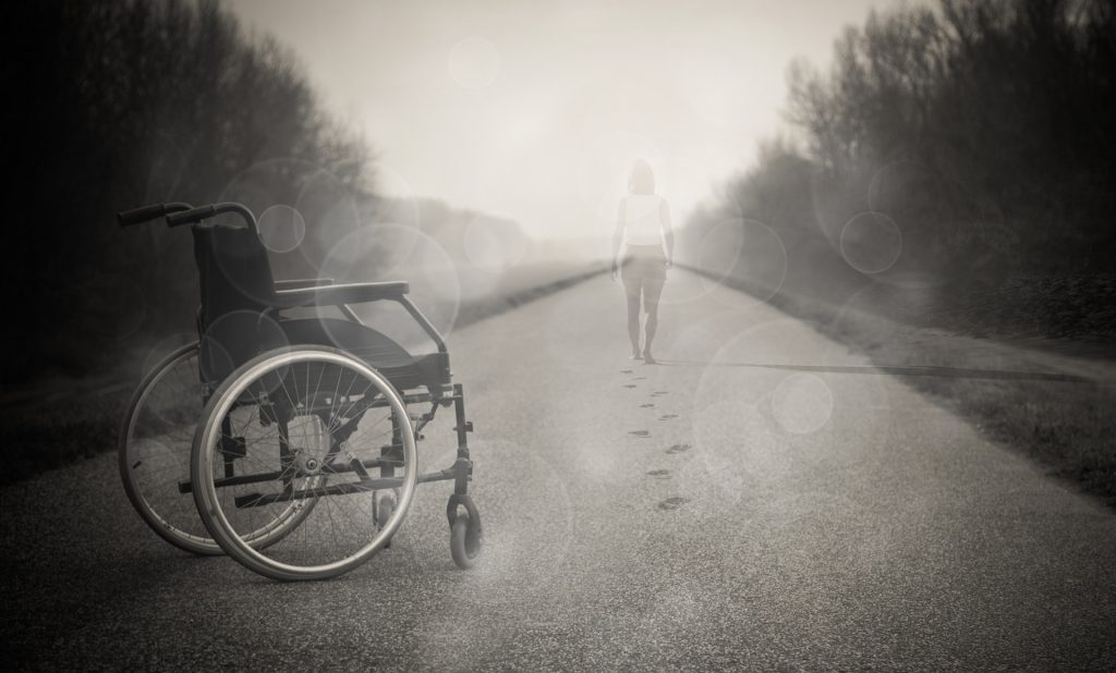 Photo in sepia tones of a wheelchair-user standing and walking away from her wheelchair
