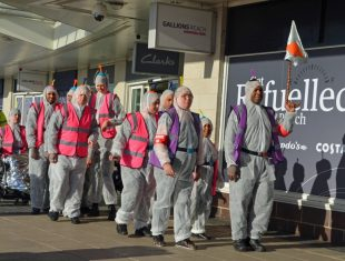 Group of people walking around London in boiler suits