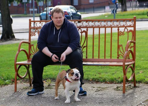 Photo of a young man on a park bench with a bulldog sat as his feet.