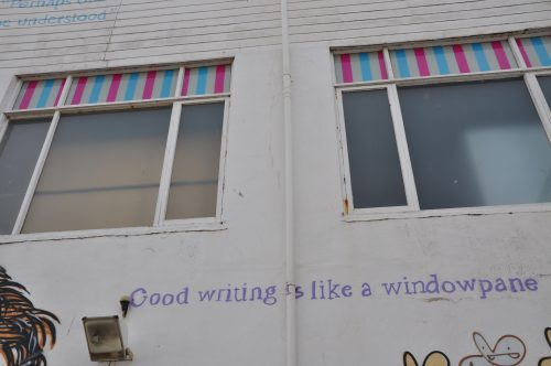Graffiti on the side of a white wall reads: 'Good writing is like a window pane'.