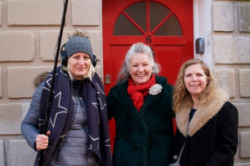 Photo of three women from the research team standing outside a red door.