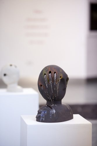 Sculpture of a head with hand print in it