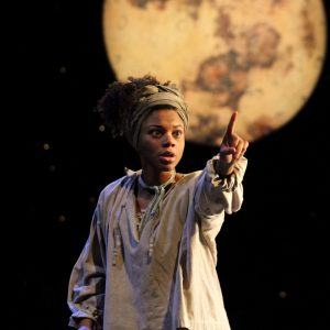 Photo of a young actress Sapphire Joy on stage with a backdrop of a large full moon