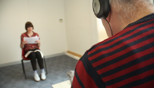 Film still of the back of a man with headphones facing a woman sat in a chair reading a script
