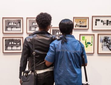 Two people from behind looking at a wall in a gallery
