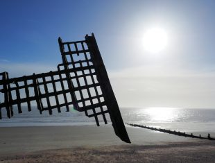 A dramatic photo of a rusty metal frame on the seashore