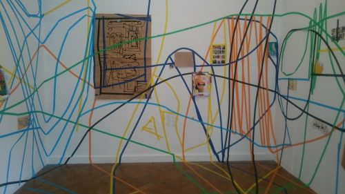 Exhibition shot, with walls and floor covered in coloured tape