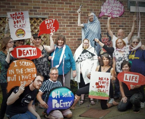 """Image shows 14 cast members with signs which read: 'DEAD PEOPLE DON'T CLAIM', 'Don't Eat Us', 'Death', 'I scream in the street but I have no mouth', 'Oh Shit Poetry', 'QUEER DISABLED SOLIDARITY', 'Life', and """"If the system cripples you, you must cripple the system!"""" Oscar Wilde"""