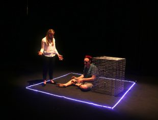 Two actors within an illuminated blue square