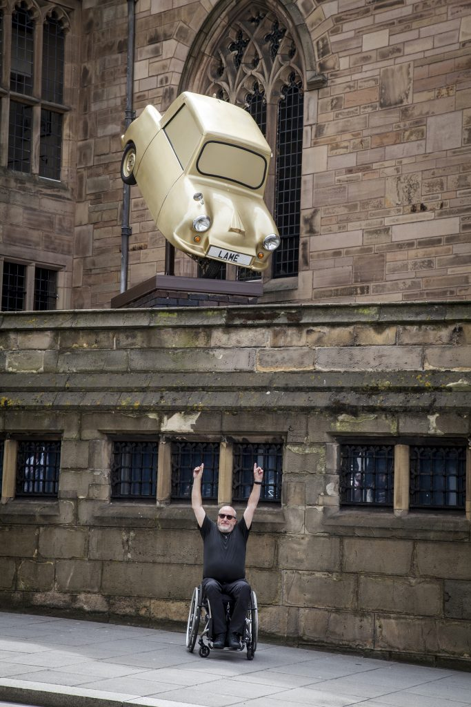 Photo of the artist Tony Heaton standing posing beneath his sculpture of an invalid carriage sprayed with gold.