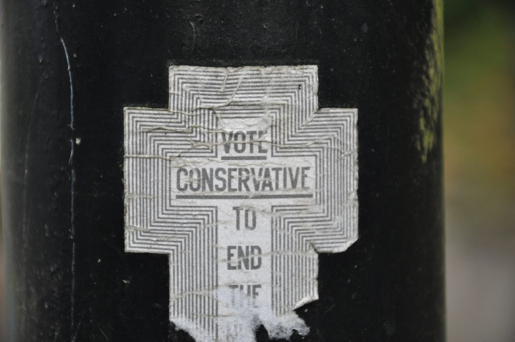 "A crumpled sticker in the shape of a cross with concentric lines and the words ""vote conservative to end the..."""