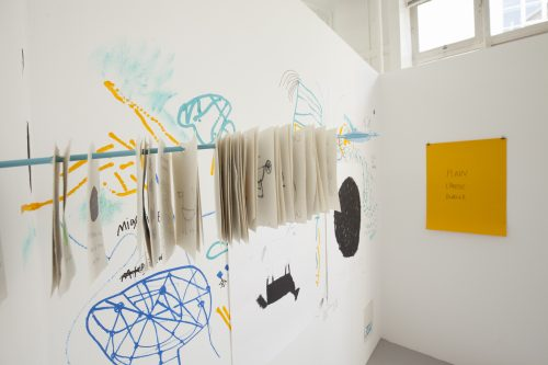 Installation shot showing an arrow with drawings on it