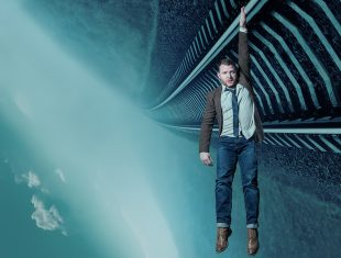Train track and the sky, flipped to landscape. A man in jeans, a shirt and a blazer, hangs by one arm from the sideways traintracks.