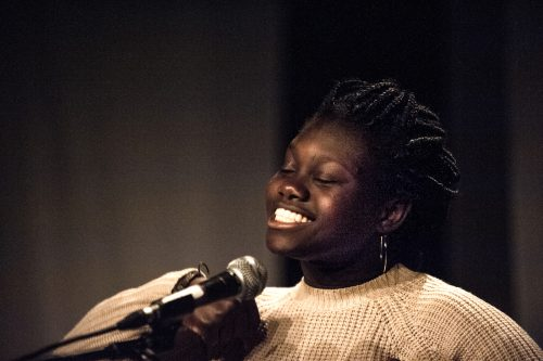 A young woman smiles into a microphone