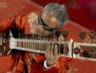 Blind sitarist Baluji Shrivastrav holds his sitar