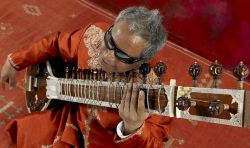 Blind sitarist Baluji Shrivastrav holds his sitar