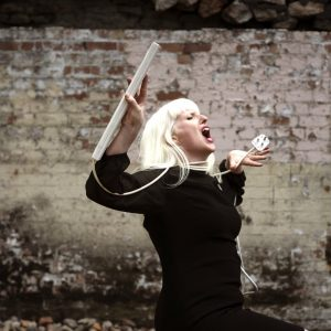 A young woman with white hair declaims, mouth open, posing against a brick wall