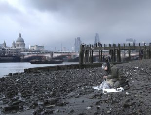 Atmospheric photo of artist Liz Crow sitting on the mudbanks of the Thames river