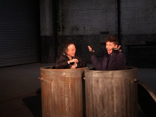 Two disabled women chat and laugh from within two very large dustbins,