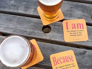 Photo of two pints of beer and beer mats with the artists' slogan