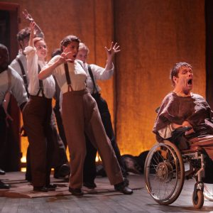 Jamie Beddard sits in a wheelchair, to the right of the image, followed by a group of actors behind
