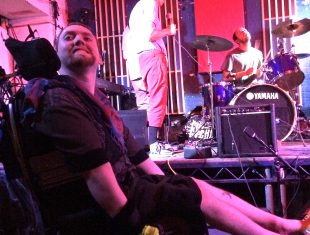 performer Demented Dave smiles from his chair