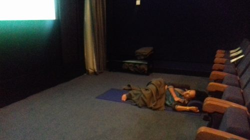 Woman lying down at the front of a cinema
