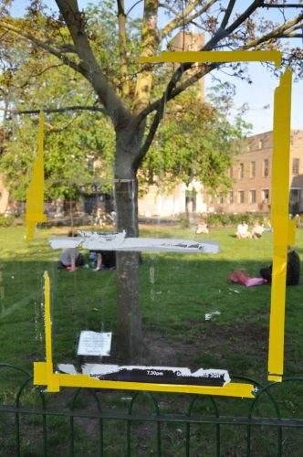an empty yellow frame is set up in front of a tree in a park