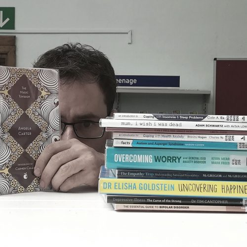 Man hiding behind a book