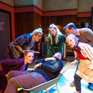 Five actors huddle around a sixth actor lying in a wheelbarrow