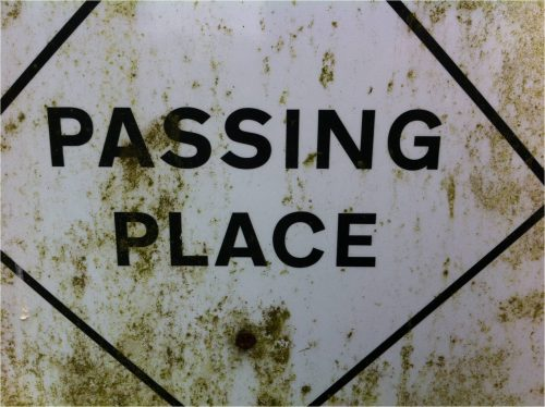 Image of a weathered sign with the words 'passing place'