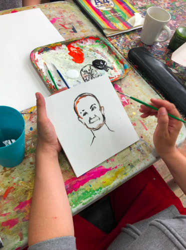 A small portrait drawing rests in the hands of the artist