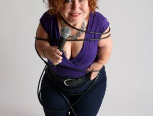 Photo of comedian Tanyalee Davis tangled up in a microphone cord