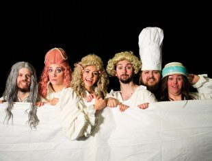 The cast of the Flop in oversized wigs