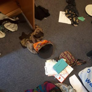 Clothes and other mess strewn on the floor