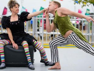 a female dancer holds back a male dancer who leans towards her