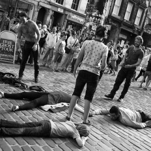 Street perfomers lying on a cobbled street