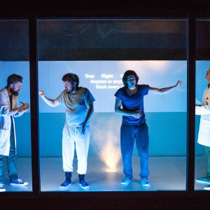 Behind blue-tinted glass screen four male actors pose as doctors and patiends