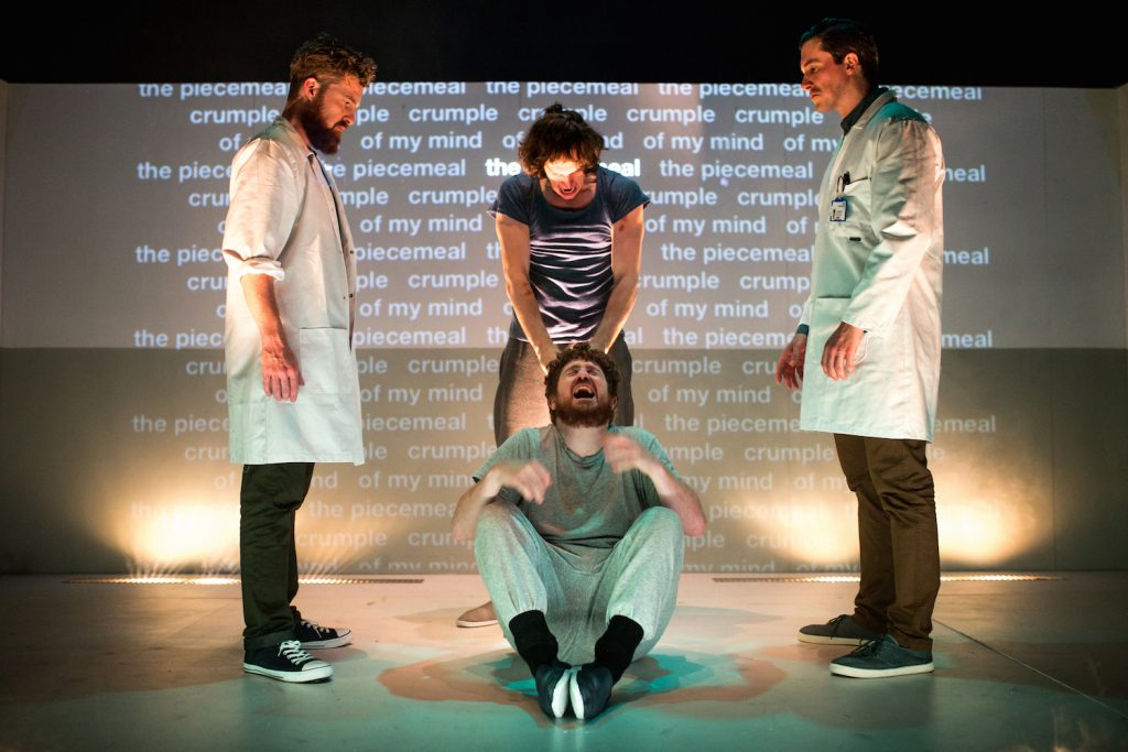 A male actor with a pained expression, sits centre stage, another actor stands behind him and two more in white coats stand either side