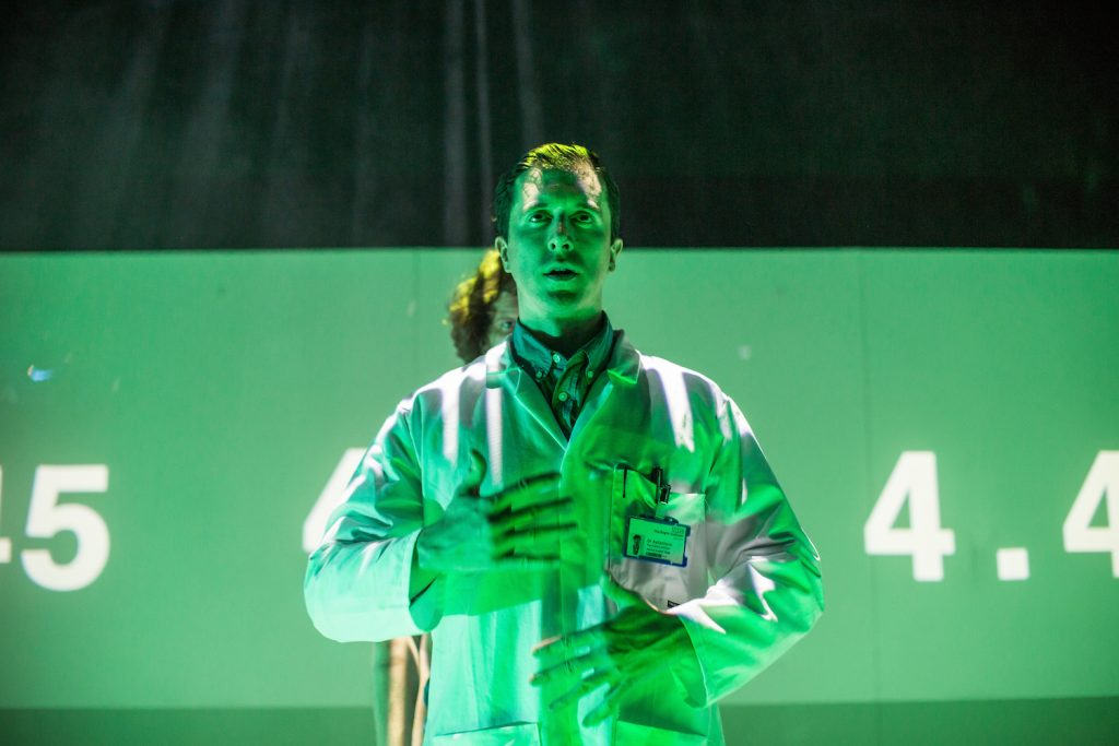 Dressed in a white coat, a male actor poses centre stage under a green light